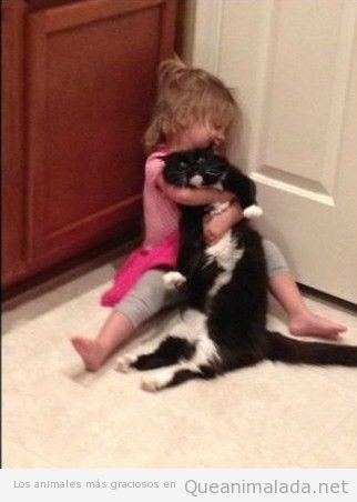 Niña graciosa abraza sin mesura a su gato, que está harto de ella
