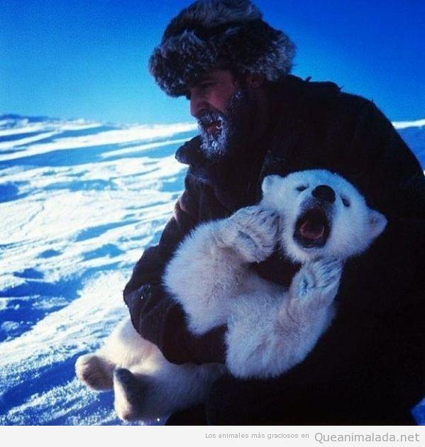Imagen bonita de un oso polar bebé en brazos de un hombre