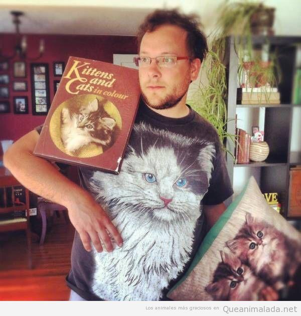 Foto curiosa de un hombre con camiseta, libro y cojines de gatos